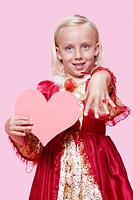 Portrait of a happy young girl dressed in princess costume holding paper heart as she displays ring over pink background