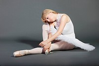 Upset young female ballet dancer sitting over grey background
