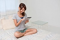 Young Woman Sitting on Bed and Looking Tablet PC