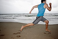 Young man running on beach
