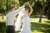 Hispanic grandfather dancing with bride