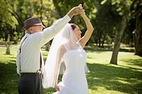 Hispanic grandfather dancing with bride