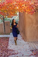 Hispanic woman carrying coffee and text messaging on cell phone