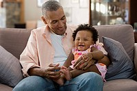 Black father holding daughter on his lap