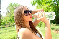 Profile of beautiful woman drink some water from plastic bottle