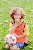Caucasian girl sitting in grass with soccer ball