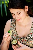Woman adding lime juice on an avocado.