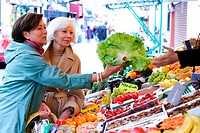 Woman and elderly woman shopping for fruits.