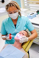 Dentist using ultra violet light to activate teeth withening solution.