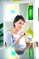 Woman putting essential oils in diffuser.