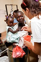 Mothers and children suffering from malnutrition receiving food rations. Program of ambulatory treatment of malnutrition implemented by a local non_go...