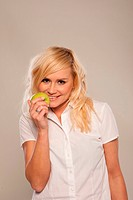 Smiling blonde with green apple