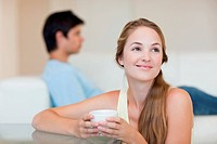 Woman drinking coffee while her fiance is sitting on a couch