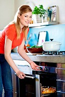 Woman using oven.
