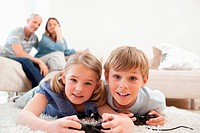 Playful children playing video games with their parents on the background