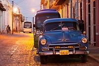 Cuba, Sancti Spiritus Province, Trinidad, taxis on Calle Antonio Maceo, dusk