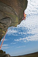 Rock climber scaling rock formation