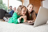 Germany, Bavaria, Nuremberg, Girl and boy using laptop in living room