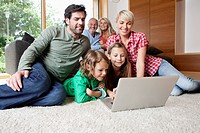Germany, Bavaria, Nuremberg, Family using laptop in living room