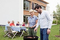 Germany, Bavaria, Nuremberg, Couple grilling barbecue, family sitting in background