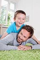 Germany, Berlin, Father and son having fun at home, smiling (thumbnail)