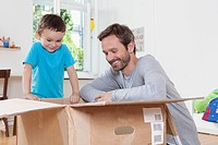 Germany, Berlin, Father and son opening parcel box