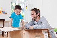 Germany, Berlin, Father and son opening parcel box (thumbnail)