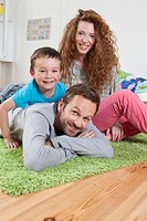 Germany, Berlin, Family lying on floor, smiling, portrait