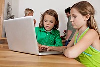 Germany, Bavaria, Nuremberg, Girl and boy using laptop in kitchen