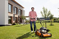 Germany, Bavaria, Nuremberg, Mature man with lawn mower in garden (thumbnail)