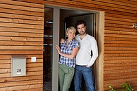 Germany, Bavaria, Nuremberg, Mature couple standing at front door of house