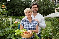 Germany, Bavaria, Nuremberg, Mature couple with vegetables in garden