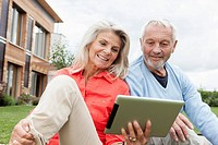 Germany, Bavaria, Nuremberg, Senior couple using digital tablet in garden