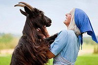 Germany, Bavaria, Mature woman with goat on farm