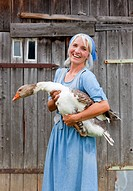 Germany, Bavaria, Mature woman with goose on farm