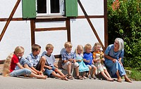 Germany, Bavaria, Woman sitting with group of children in front of small house