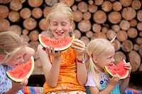 Germany, Bavaria, Girls eating watermelon