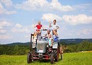 Germany, Bavaria, Woman with group of children sitting in old tractor