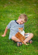 Germany, Bavaria, Boy with cat on farm