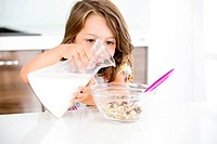 Germany, Girl pouring milk in muesli