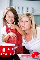 Germany, Mother and daughter eating noodles in kitchen