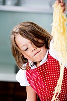 Germany, Girl playing with spaghetti (thumbnail)