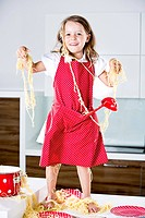 Germany, Girl playing with spaghetti on kitchen worktop