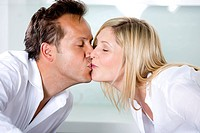 Germany, Mid adult couple eating noodles and kissing