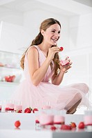 Germany, Young woman with glasses of strawberry yogurt, smiling