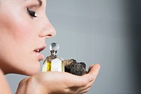 Young woman holding truffles and truffle oil, close up