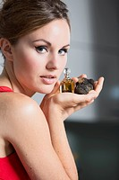 Young woman holding truffles and truffle oil in her hand, close up