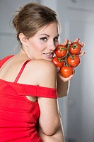 Germany, Young woman holding tomatoes in her hand