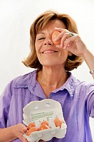Senior woman holding egg in front of eye, smiling