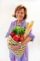 Senior woman with vegetable shopping bag, smiling, portrait